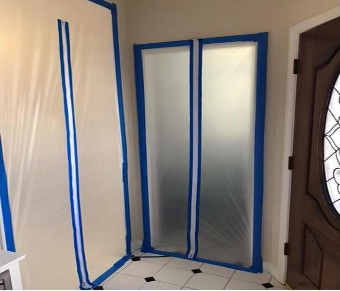 Same bathroom area with the same checkered style flooring but with plastic containment covering the doorway with blue tape.