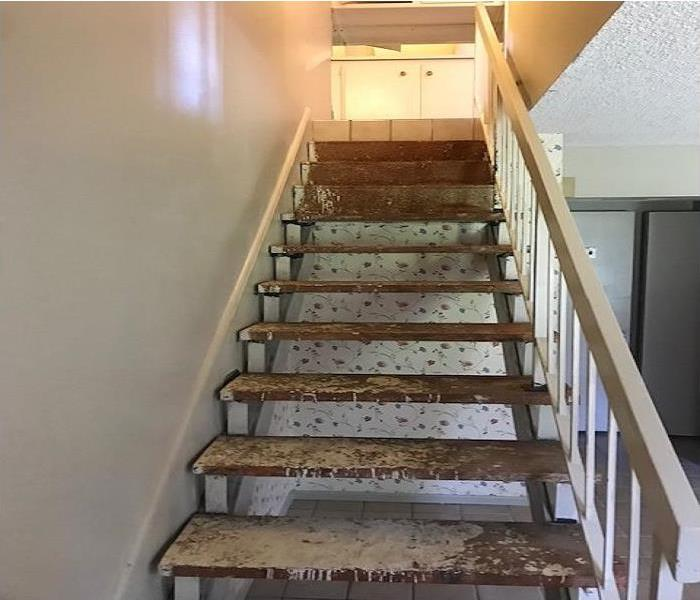 Stairway that is stripped of the brown and dirty carpet. Wood stairway.