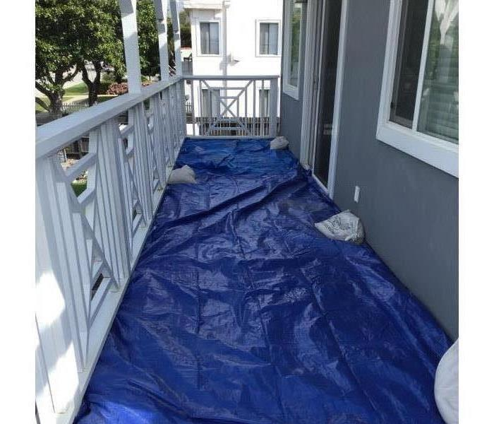 Blue tarp with sand bags is covering the balcony floor.