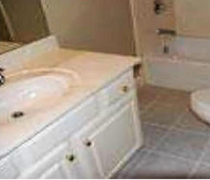 White colored vanity and sink area that is clean and spotless
