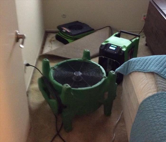 Entrance of a bedroom of a carpeted bedroom and has an air mover and a dehumidifier.