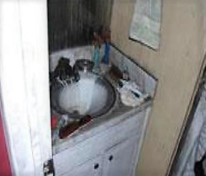 Vanity and sink area, which has soot and ashes from a fire.