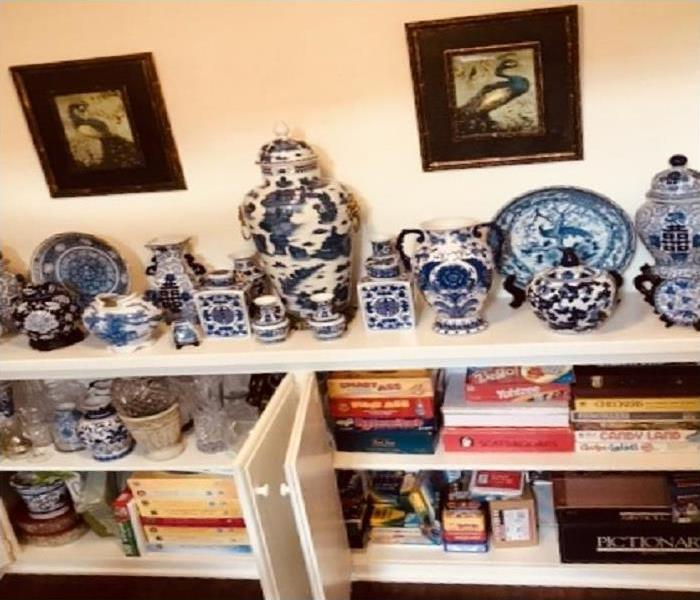 Lower cabinet filled with items that are antique or vintage with vases and plates displayed above that are fragile.