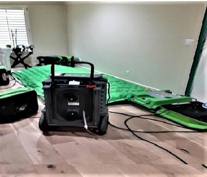Living room with hardwood floors but with our drying mat system, 1 dehumidifier and a few air movers.