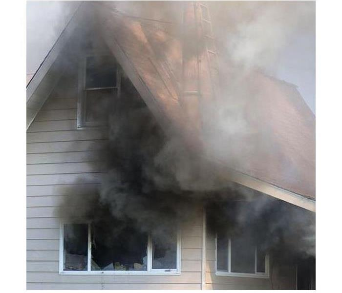 A Home with black smoke coming out of broken shattered windows