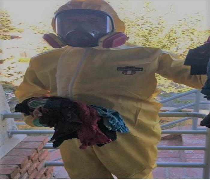 Technician fully clothed in a PPE and full mask, holding dirty rags to clean biohazard