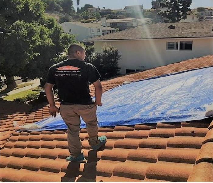Technician on top of a roof, with the blue tarp covering the spanish tile. Overlooking the neighborhood.