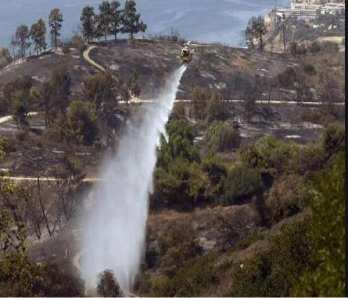 Helicopter pouring water over the hillside of Palos Verdes Estates dousing a brush fire.