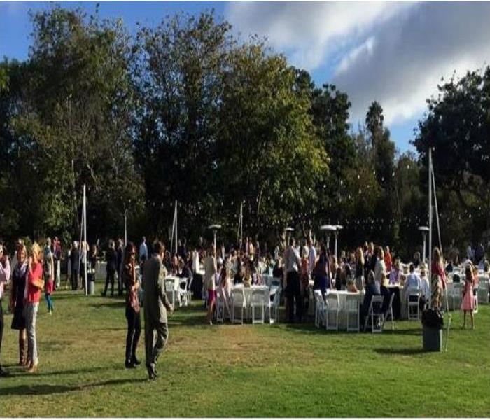 Grassy area with white portable chairs and tables under an array of trees and christimas lights with lots of community people