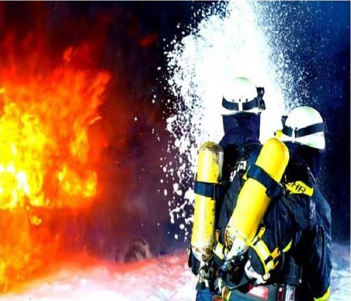 2 firefighter spraying down a very large fire with foam.
