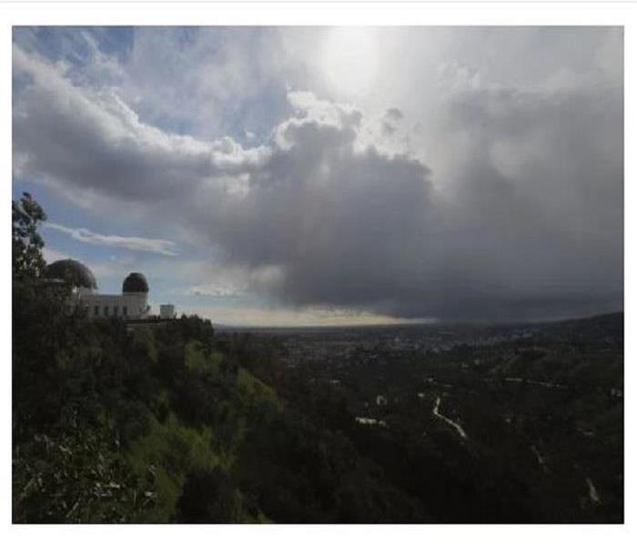Mountainside of Griffith Park Observatory under dark clouds.
